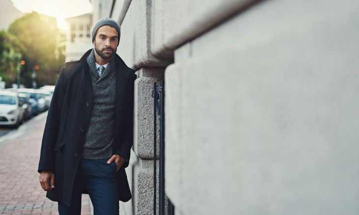 man_in_sweater_and_coat_leaning_against_building_wall_jpeg-1080x648